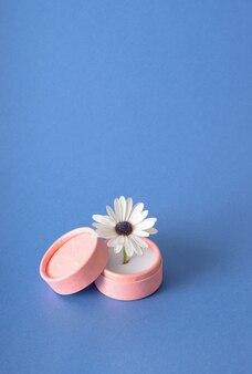 青い背景のリングボックスに白い花。シュールなエンゲージメントのコンセプト。