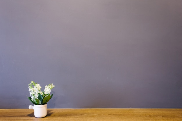 White flower vase put on the table with brick wall interior room.