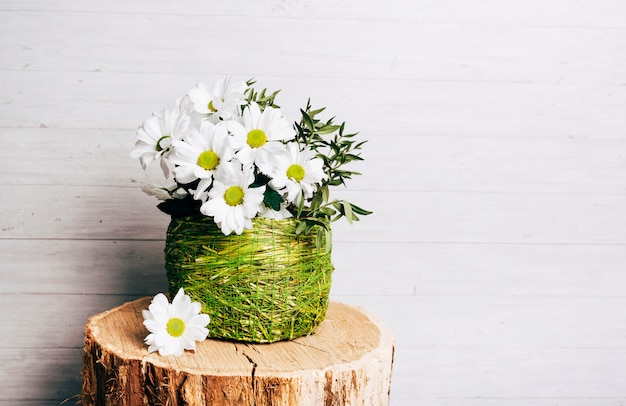 White flower vase on tree stump against wooden background