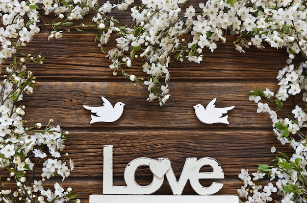White flowering cherry tree branches with two wooden birds and letters love.