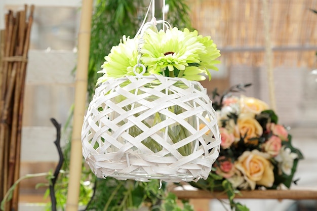 White flowerpot with green flowers hanging