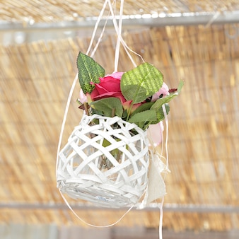 White flowerpot with pink flowers hanging