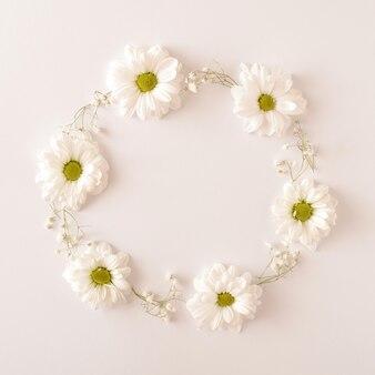 白い背景の上に円形に配置された白い花。春の結婚式の婚約の概念。フラットレイフレーム。