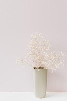 ピンクの花瓶に白い花の花束。最小限の休日の概念。