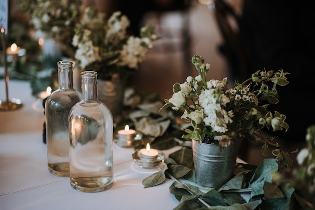 White flowers in a bucket, water bottles and candles on a table decorated with leaves