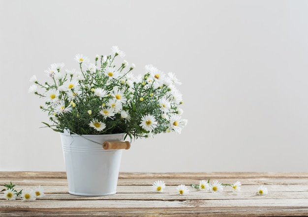 White flowers on bucket on wooden table