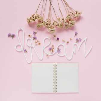 White flowers bunch and lavender flowers on dream text with an open diary over pink backdrop