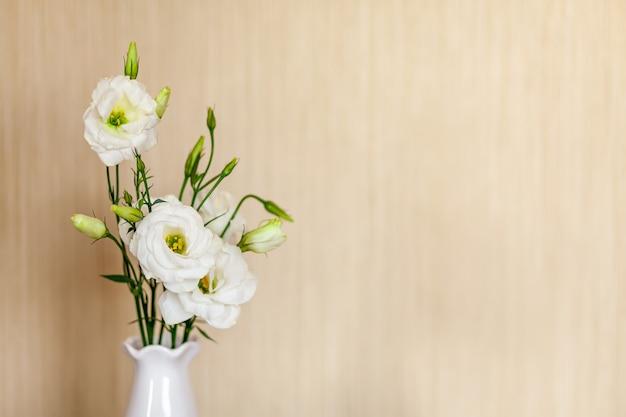 コピースペースのある木製のテーブルの上に花瓶に白い花ユーストマまたはトルコギキョウ。
