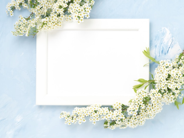 White flowers over the frame on blue concrete background.