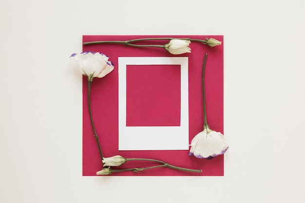 White flowers frame surrounding an empty piece of paper with photo frame