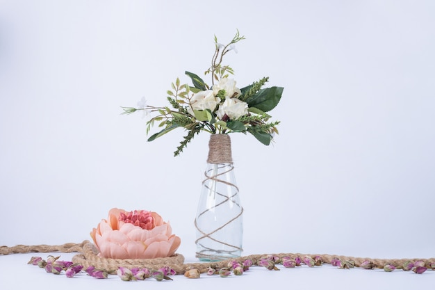 White flowers in glass vase on white with single rose.
