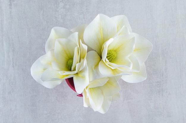 흰색 바탕에 분홍색 양동이에 흰색 꽃. 고품질 사진