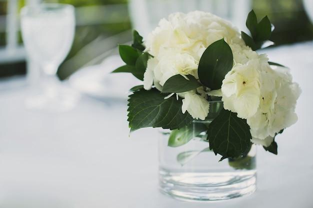 Белые цветы в вазе на свадебном столе