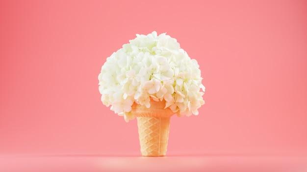 Белые цветы в вафельном рожке мороженого на розовой стене.