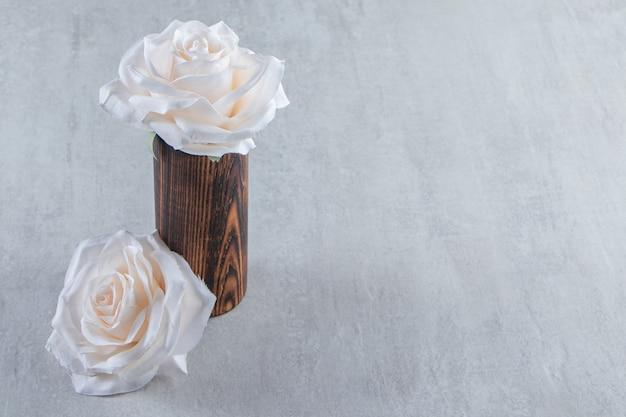 白いテーブルの上に、木製の水差しの白い花。
