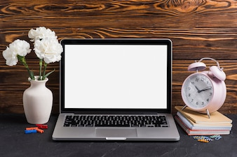 White flowers in the vase; laptop and alarm clock on notebooks against wooden backdrop