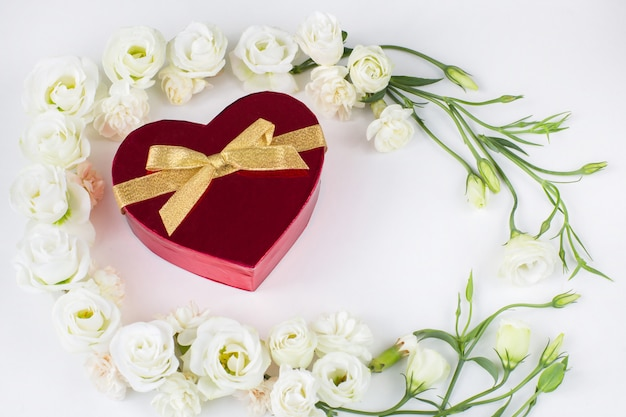 White flowers lined with a frame and a red heart-shaped box