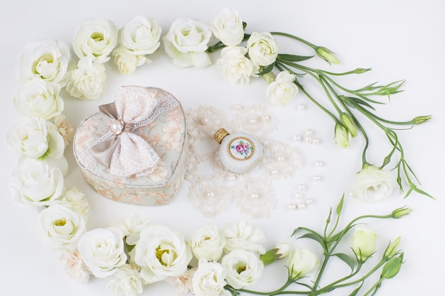 White flowers lined with a heart-shaped jewelry box, perfume bottle, pearls and lace
