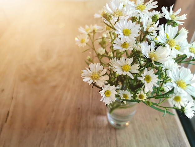 White flowers in metal pot on the wooden table