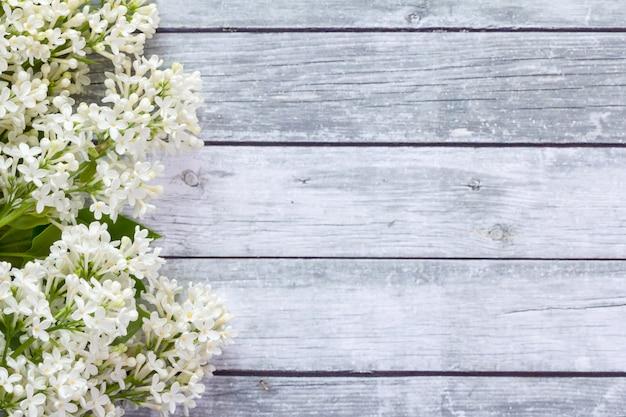 木製の背景に白い花。