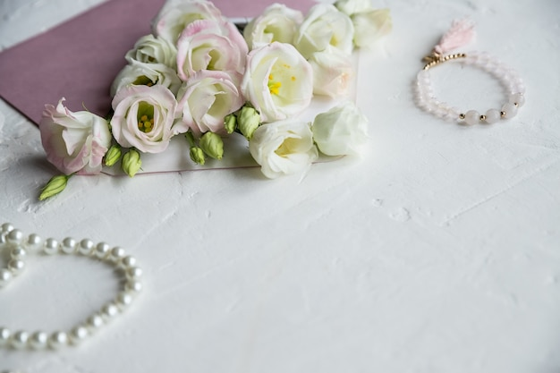 White flowers, pearls necklace, perfume, greeting card on white.accessories and flowers. online shopping or dating concept with copy space.