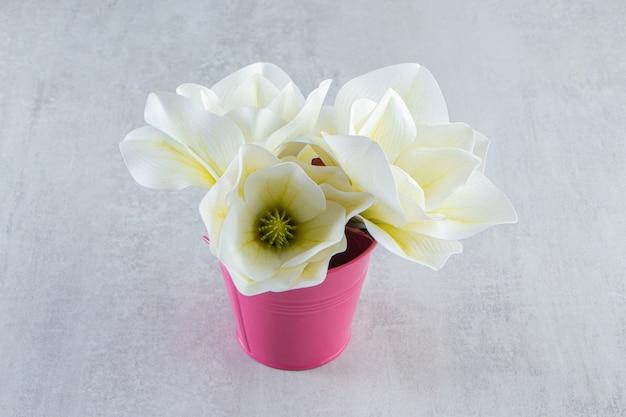 Fiori bianchi in un secchio rosa, sul tavolo bianco.