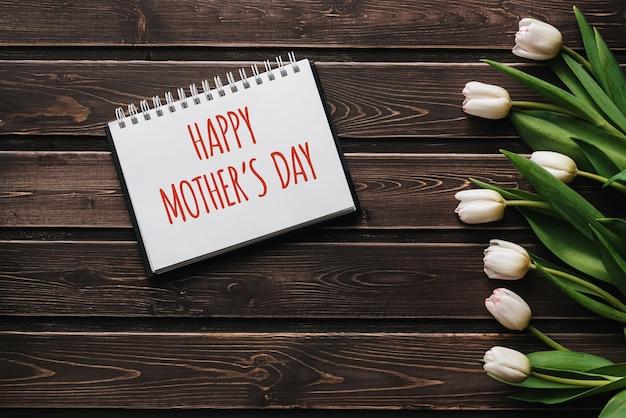 木製の茶色のテーブルボード上の白い花チューリップ。幸せな母の日をレタリングとグリーティングカード