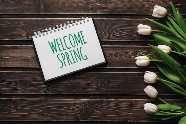 木製の茶色のテーブルボード上の白い花チューリップ。ようこそ春をレタリングとグリーティングカード