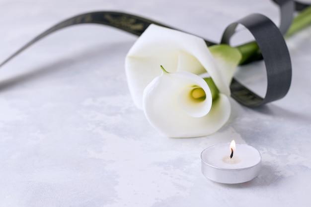 Белые цветы с траурной лентой