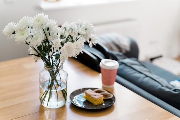 木製のテーブルにコーヒーとケーキと白い花