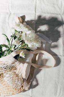 白い背景の上の手作りのバッグの中にスプレーボトルと白い花