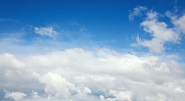 White fluffy clouds in the blue azure sky. summer good weather background.