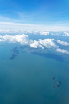 Белые пушистые облака летят над океаном и островами. фото с самолета.
