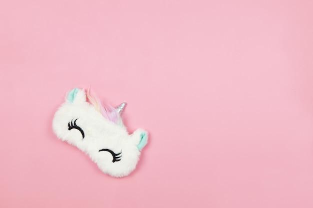 パステルピンクの紙の背景に目を閉じて小さな耳を持つ白いふわふわの毛皮の睡眠マスクユニコーン