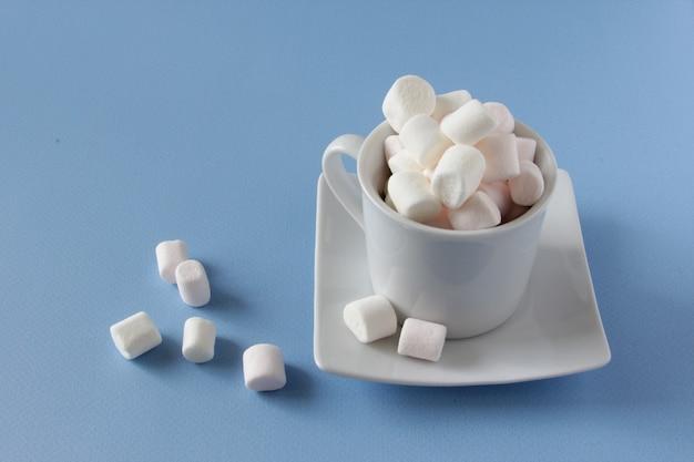 파란색 배경에 고립 된 흰색 컵에 흰색 솜 털 마시멜로 파란색 배경에 마시멜로