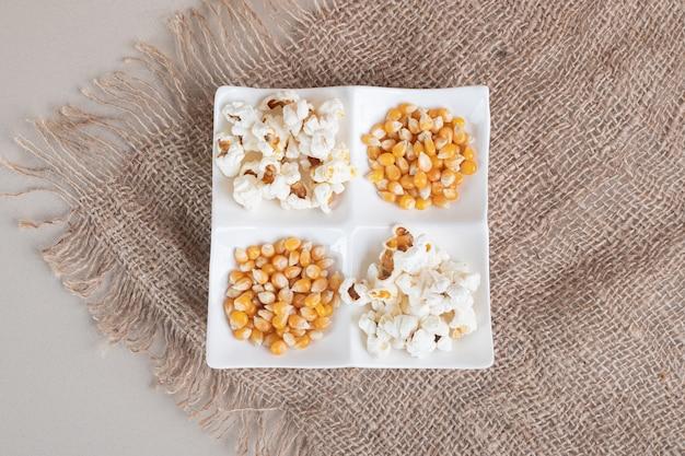 Popcorn soffici bianchi in una tazza di ceramica su cemento.