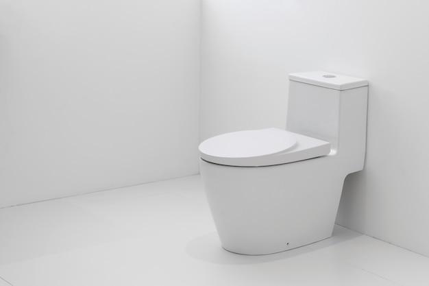 Белый туалет со сливом в белой ванной комнате.