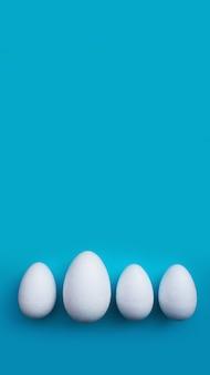 Белые яйца пены на синем фоне. плоская планировка, вид сверху. концепция пасхи.