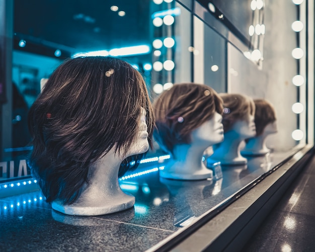 White foam female mannequins heads in a row on a store window at night