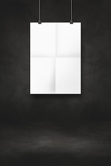 White folded poster hanging on a black wall with clips. blank mockup template