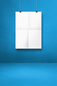 White folded poster hanging on a blue wall with clips. blank mockup template