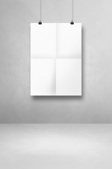 White folded poster hanging on a clean wall with clips. blank mockup template