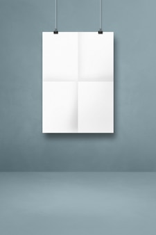 White folded poster hanging on a grey wall with clips. blank mockup template