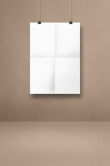 클립이 있는 베이지색 벽에 매달려 있는 흰색 접힌 포스터. 빈 모형 템플릿
