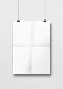 クリップできれいな壁にぶら下がっている白い折り畳まれたポスター。