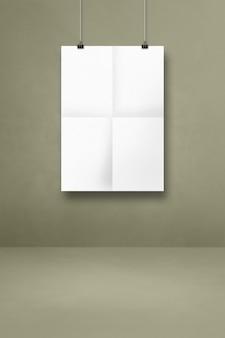 클립이 있는 회색 벽에 흰색 접힌 포스터가 걸려 있습니다. 빈 모형 템플릿