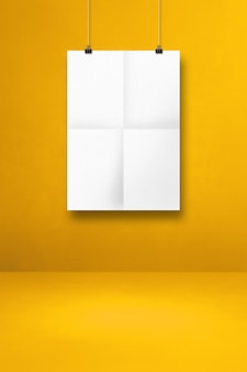 클립이 있는 노란색 벽에 흰색 접힌 포스터가 걸려 있습니다. 빈 모형 템플릿
