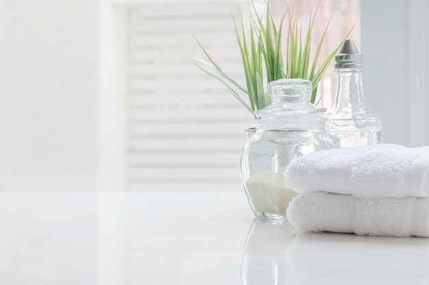 White folded towels and glass bottle on white table with copy space on blurre bathroom background.