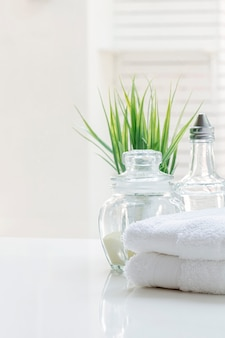 White folded towels and glass bottle on white table with copy space.