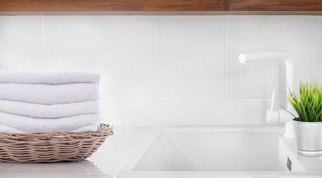 キッチンルームの白いカウンターテーブルのバスケットに白い折り畳まれたタオル